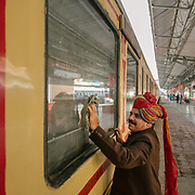 Staff cleaning the window on the Palace on Wheels, a vintage luxury train crossing Rajahstan province.