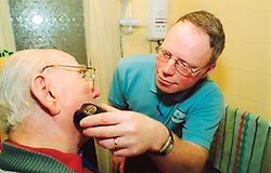 Male home helper cares for an elderly man in sheltered accommodation Yorkshire UK