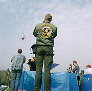 "An airshow aviation enthusiast adorned with badges enjoy aerobatic activity above their heads at Biggin Hill, Kent, England. As a helicopter banks tightly to the right, other groupies film something else to the left from the public areas during the many varied flying displays  at this small airfield north of London that saw action as an important airfield during the WW2 Battle of Britain, a location for the ""Operations Room"" for the Operation Crossbow V-1 flying bomb defences."