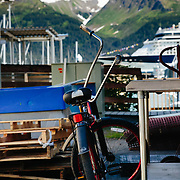 A townie chopper bike is parked with the mountains and a cruise ship parked in the background in Seward, Alaska.