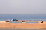 A man lying on a bench sleeping, on the riverside seaside walk along the river Rio de la Plata Ramblas Sur, Gran Bretagna and Republica Argentina Montevideo, Uruguay, South America