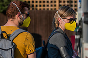 A couple in matching masks head to the mini Sainsburys at the petrol station -  The 'lockdown' continues for the Coronavirus (Covid 19) outbreak in London.