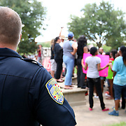 A Longwood Police officer watches as demonstrators voice their opinions by singing and holding up signs in the protest area, prior to the trial of George Zimmerman at the Seminole County Courthouse, Saturday, July 13, 2013, in Sanford, Fla. Zimmerman had been charged for the 2012 shooting death of Trayvon Martin. Zimmerman was found not guilty by a jury of six women. (AP Photo/Alex Menendez)