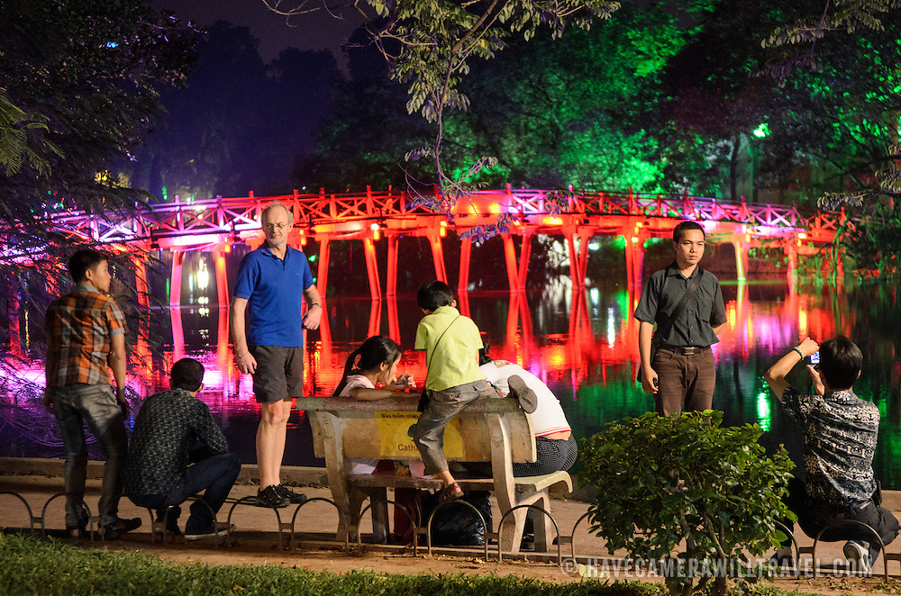Tourist pose for photos on the banks of Hoan Kiem Lake in front of The Huc Bridge (Morning Sunlight Bridge) at night. The red-painted, wooden bridge joins the northern shore of the lake with Jade Island and the Temple of the Jade Mountain (Ngoc Son Temple).