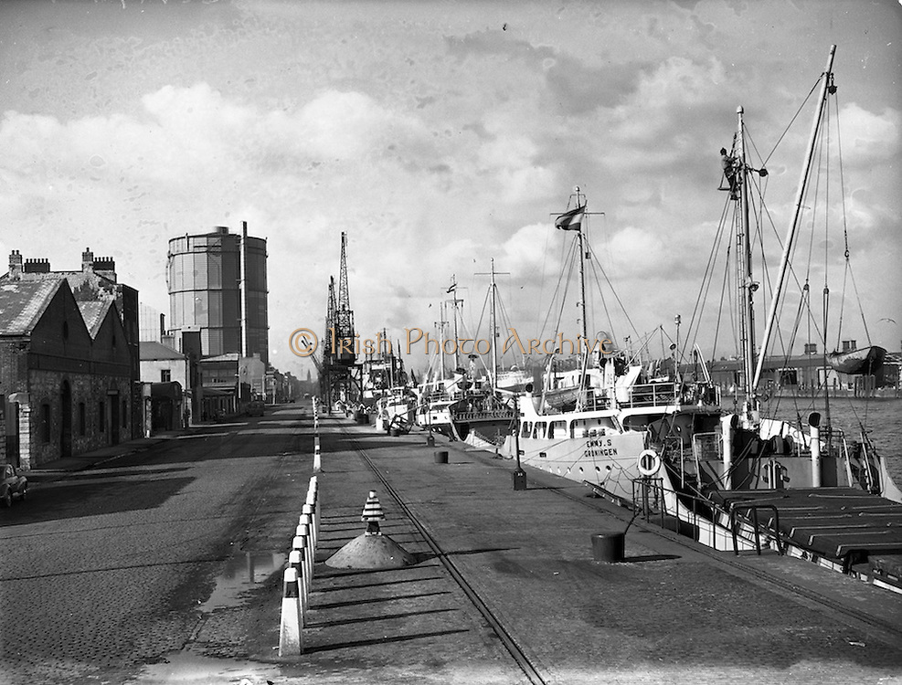 """113/02/1958<br /> 02/13/1958<br /> 13 February 1958<br /> Docks strike: Dublin Port and Alexandra Basin Dock Strike. The docks lie deserted during the strike except for a few trucks, with a view of the """"Emmy S."""" out of Groningen, and other ships."""