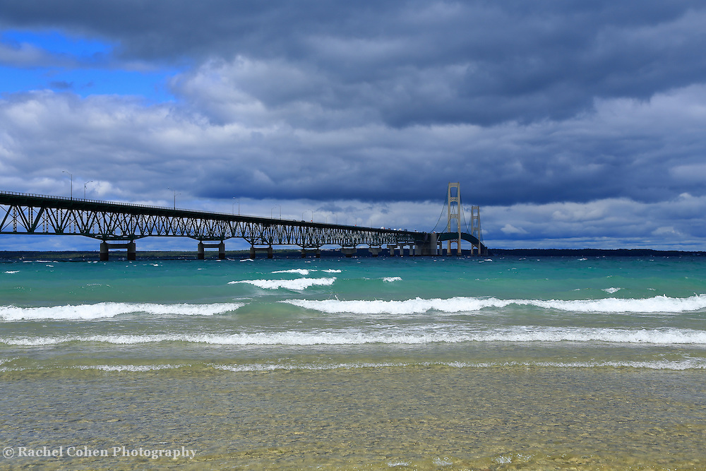 """""""Span the Straits"""" 2 <br /> <br /> The beautiful Mackinac Bridge crossing over the straits of Mackinac. Layers of clouds, and colors of water and waves in all hues of blue!!<br /> <br /> Mackinac Bridge by Rachel Cohen"""