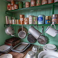 Vintage foodstuffs and cookware line shelves in the kitchen of a hut at Port Lockroy, an abandoned British Science base on Goudier Island, Antarctica that has been restored as a museum.