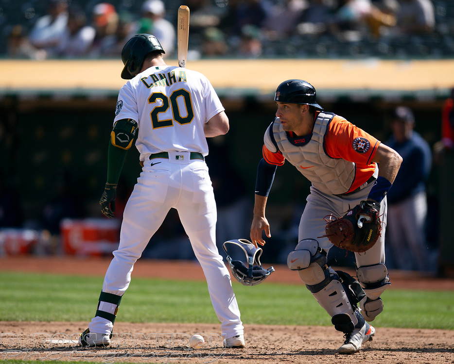 Sep 26, 2021; Oakland, California, USA; Houston Astros catcher Jason Castro (18) pursues a loose ball as Oakland Athletics left fielder Mark Canha (20) bats in the third inning at RingCentral Coliseum. Mandatory Credit: D. Ross Cameron-USA TODAY Sports