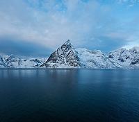 Olstind mountain peak rises from fjord, Lofoten Islands, Norway