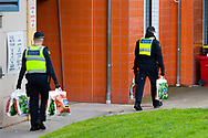 Police are seen carrying groceries into 12 Sutton Street for hungry residents amid a full and total lockdown of 9 housing commission high rise towers in North Melbourne and Flemington during COVID-19 on 5 July, 2020 in Melbourne, Australia. After 108 new cases where uncovered overnight, the Premier Daniel Andrews announced on July 4 that effective at midnight last night, two more suburbs have been added to the suburb by suburb lockdown being Flemington and North Melbourne. Further to that, nine high rise public housing buildings in these suburbs have been placed under hard lockdown for a minimum of five days, effective immediately.  Residents in these towers will not be allowed to leave their units for any reason. Police will be stationed at every entry and exit point, every level, and they will also surround these locations preventing any movement in, or out. There is a total of 1354 units and over 3000 residents living in these buildings including the states most vulnerable people. These new restrictions will remain in place for fourteen days with fears of further lockdowns to come. The Government have stressed that if Victorians do not follow the basic COVIDSafe rules, the whole state will go back in to lockdown. (Image by Dave Hewison/ Speed Media)