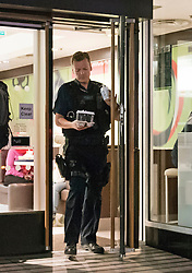 © London News Pictures. 30/04/2015. A member of the Metropolitan police leaving a McDonald's restaurant in Victoria, London holding three drinks, while is colleagues wait in a police vehicle, parked on double yellow lines and using emergency lights. The police vehicle was blocking one lane of a busy road leading from Westminster through central Victoria. When the officer returned to the police vehicle the emergency lights were turned off. Photo credit: LNP