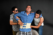 a young man suffering lower back pain is helped by his friends
