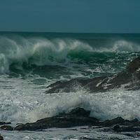 Cormorants watch waves crash ashore at Bean Hollow State Beach on the California coast near Pescadero, California.