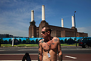 Street scene with a tattoed man beside Battersea Power Station in South London. This classic Art Deco brick design with it's distinctive four white towers is one of London's most famous landmarks. Now derelict and with plans for possible development, it remains one of the iconic designs which towers over the River Thames.