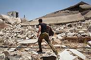 An FSA soldier runs amongst the ruins of a number of homes in Sarmin, Idlib. The town has been repeatedly attacked by the Syrian military causing huge damage, and the lives of many residents. Idlib province in Syria's northwest is one of the few areas in Syria which is currently under FSA control, although this control is patchy and ever shifting. Sarmin, Idlib, Syria. 18/06/2012