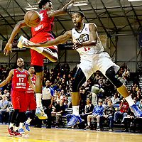 Bakersfield Jam guard Jerel McNeal makes a mid-air pass around Grand Rapids center Hasheem Thabeet during the Jam's 105-99 victory in the championship game of first-ever NBA D-League Showcase Cup at Kaiser Permanente Area in Santa Cruz, California.<br /> Photo by Shmuel Thaler <br /> shmuel_thaler@yahoo.com www.shmuelthaler.com
