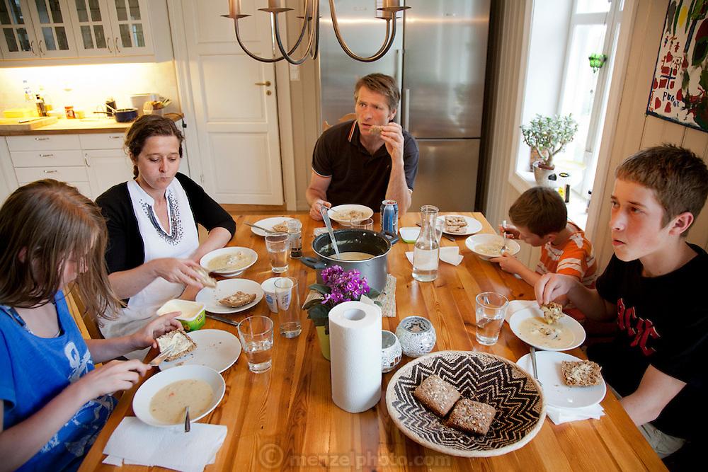 The Glad Ostensen family in Gjerdrum, Norway. Anne Glad Fredricksen, 45, her husband Anders Ostensen, 48, and their three children, Magnus, 15, Mille 12, and Amund, 8 at an evening meal in their farmhouse kitchen. Model-Released.