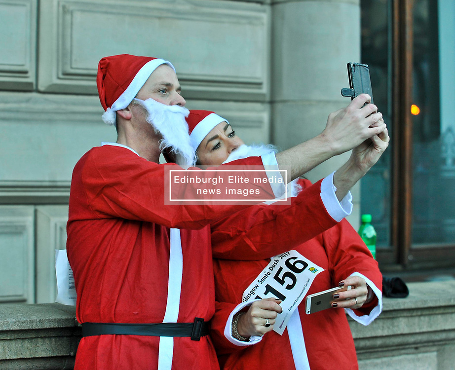 Andrea Daly and Martin Mccluskey from Kilmarnock take a quick selfie before more than 8000 runners, all dressed as Santa, took part in the annual charity fun run thru the centre of Glasgow, to raise money for charity.<br /> <br /> © Dave Johnston/ EEm