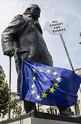 © Licensed to London News Pictures. 23/06/2018. London, UK. A protester holds a placard saying 'We fought for Europe' infront of a statue of wartime leader Winston Churchill as The People's Vote March for a second EU referendum reaches Parliament Square. Photo credit: Peter Macdiarmid/LNP