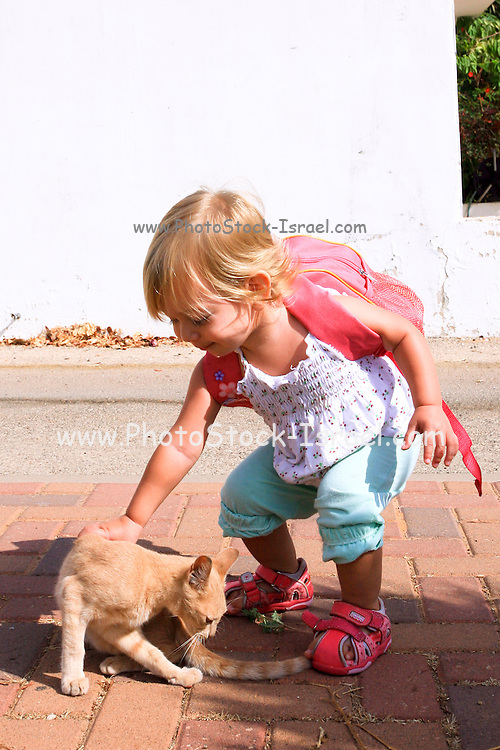 A 18 month toddler girl, with a small lunch pack ready for kindergarten saying goodbye to her cat