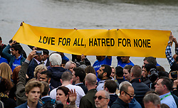 © Licensed to London News Pictures. 05/06/2017. London, UK. A banner held up during a minutes silence at a vigil at Potters Fields Park outside City Hall in London for those who lost their lives in the London Bridge terror attack. Three men attacked members of the public  after a white van rammed pedestrians on London Bridge. Ten people including the three suspected attackers were killed and 48 injured in the attack. Photo credit: Ben Cawthra/LNP