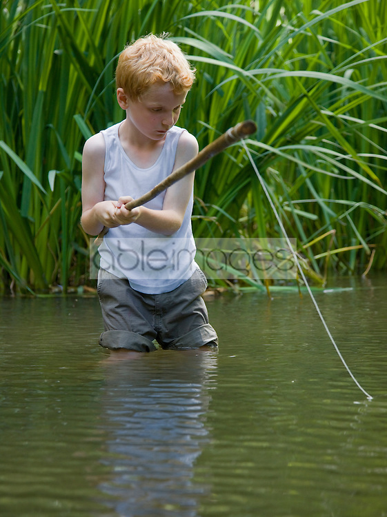 Young boy fishing in a river with his legs in the water