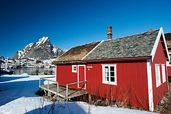 Traditional red wooden Rorbu fisherman`s hut in village of Reine in Lofoten Islands in Norway