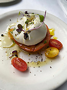 Mozzarella and tomato Caprese salad with some watercress and grape tomatoes in oil