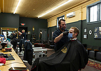 "Keeping with the social distancing guidelines Polished and Proper opens for business on Monday.  Gina Nadeau gives Howard Phelps a fresh cut and Ross Bartlett gets a haircut from Sam ""Harvard"" Ferrante Monday afternoon.  (Karen Bobotas/for the Laconia Daily Sun)"