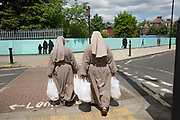 Two nuns, recently arrived in London to establish and teach the gospel, walking with shopping bags on 7th June 2017 on Streatham Hill, South London, United Kingdom