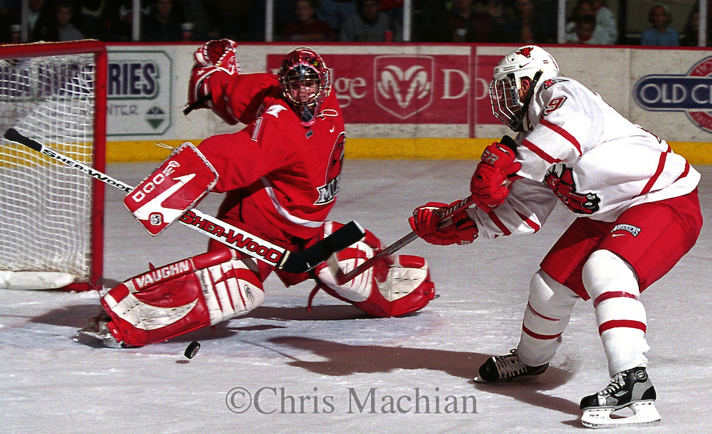University of Nebraska at Omaha's Jason Saworski tris to get the puck past the Miami of Ohio goalie in a recent game. <br /> (photo by Chris Machian/Prairie PIxel Group)