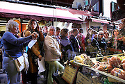 Bologna,  russian tourists in front of a gastronomy shopwindow