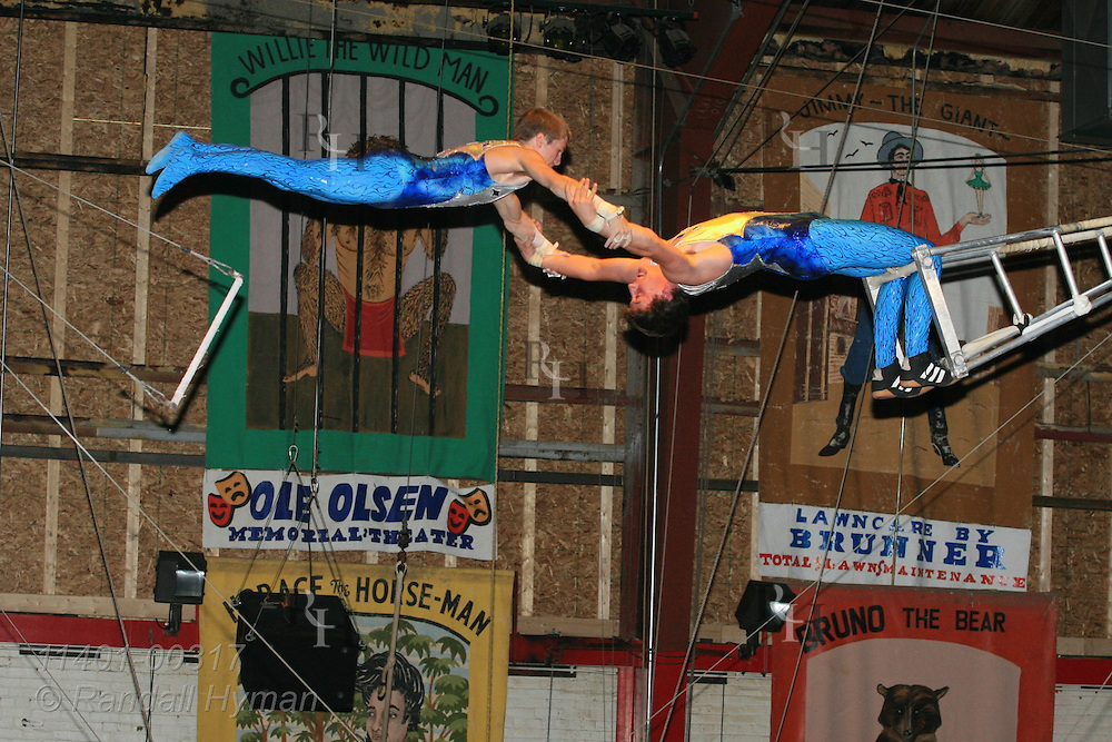 Teen performers swing high July crowds in flying trapeze act at annual Peru Amateur Circus; Peru, Indiana.