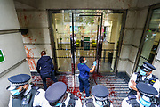 Two cleaners appear to be cleaning windows of Great Minster House, outside Department for Transport after members of Extinction Rebellion activists group pelted red colour in protest of HS2 construction. XR is protesting the construction of HS2 outside the Department for Transport in Horseferry Road in central London on Friday, Sept 4, 2020. There are other Extinction Rebellion protests ongoing in London. Police closed Horseferry Road both ways and are working to open it. Environmental nonviolent activists group Extinction Rebellion enters its 4th day of continuous ten days protests to disrupt political institutions throughout peaceful actions swarming central London into a standoff, demanding that central government obeys and delivers Climate Emergency bill. (VXP Photo/ Vudi Xhymshiti)