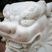 A marble lion statue at the One Pillar Pagoda. The historic, small One Pillar Pagoda sits in the center of a small pond near the Ho Chi Minh Museum in the Ba Dinh district of Hanoi. It is one of the most iconic temples in Vietnam and dates back to the 11th century.