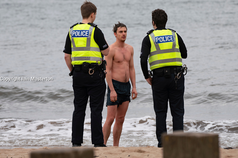 Portobello, Edinburgh, Scotland, UK. 5 April, 2020. On the second Sunday of the coronavirus lockdown in the UK the public are outside taking their daily exercise. Pictured. Police talk to man in swimming trunks on beach at Portobello. After discussion the man was allowed to continue with his swim. Iain Masterton/Alamy Live News