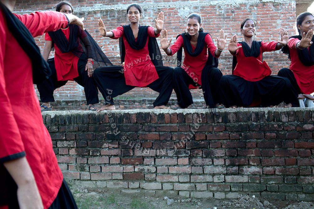 """Members of the Red Brigades are showing their martial arts skills on the streets of Madiyaw colony, Lucknow District, Uttar Pradesh. The Red Brigades are a group of young women led by Usha, 25, who after an attempted rape began talking about abuse with her students, aged around 14 to 18 years old. Usha founded the Red Brigades in November 2010. They act in self-written plays on gender equality around villages and cities, take part to protests and also teach self-defence classes. Most of the girls in the group have experienced some kind of abuse in their past. They sing words such as """"all sisters are breaking all the rules, boundaries, come to bring a new world, change will come,"""" and """"for how long do we have to go through this?"""" and """"the country has freedom, but girls do not have freedom."""""""