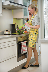 Woman talking on phone while preparing salad in kitchen