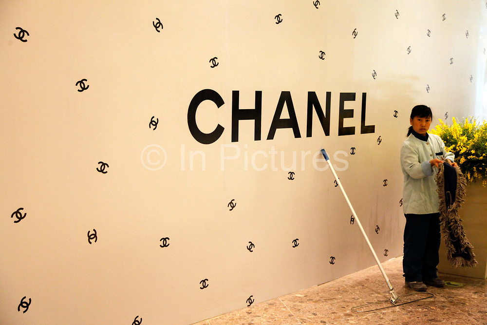 A cleaning lady works next to a soon to be opened Chanel store in Shanghai, China on 27 April 2010. China's economy reportedly grew its fastest pace in three years during the first quarter of 2010, and the country is on track to become the largest luxury goods market, past the current leaders of United States and Japan, in the next five to ten years.