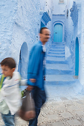 People walking past blue walls and staircase, Chefchaouen, Morocco