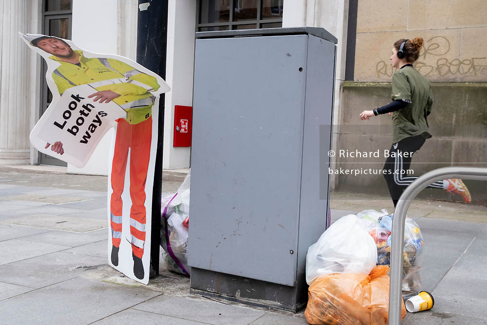 A runner passes a construction industry warning sign, erected to warn pedestrians, but damaged so that it is seemingly bending over at the waist, on 8th March 2021, in London, England.