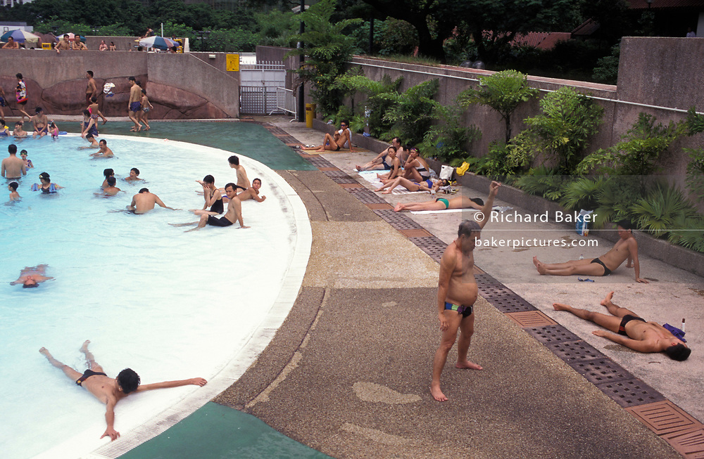 Hungarian spa customers enjoy warm pavement and thermal healing spa waters on to his wife in Budapest's famous Széchenyi thermal bath, on 18th June 1990, in Budapest, Hungary. Budapest is especially known for its spas. The Szechenyi Medicinal Bath  (Szechenyi-gyogyfurdo) is the largest medicinal bath in Europe. Its water is supplied by two thermal springs, their temperature is 74°C/165°F and 77°C/171°F, respectively. The bath can be found in the City Park, and was built in 1913 in Neo-baroque style to the design of Gyozo Czigler.