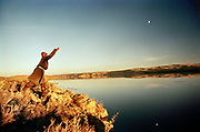 Under a half moon, beside a desert, a Mongolian nomad throws a line for fishing in the Bayan Nuur lake, Zavkhan Aimag, Mongolia.