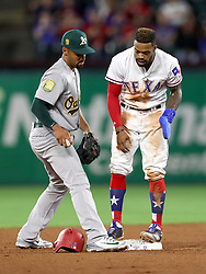April 23, 2018 - Arlington, TX, U.S. - ARLINGTON, TX - APRIL 23: Texas Rangers center fielder Delino DeShields (L) gets into second base safely in front of Athletics shortstop Marcus Semien during the game between the Texas Rangers and the Oakland Athletics on April 23, 2018 at Globe Life Park in Arlington, Texas. (Photo by Steve Nurenberg/Icon Sportswire) (Credit Image: © Steve Nurenberg/Icon SMI via ZUMA Press)