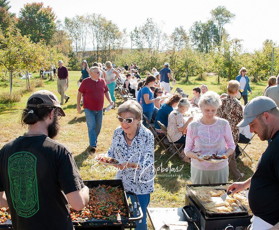 """Glenn LeClair and Chef Kevin Halligan serve up sweet potatoes with smoked chicken and arugula along with a ham, cheddar and apple omelet in addition to  during the """"Breakfast at the Orchard"""" Sunday morning at Smith's Orchard in Belmont.  (Karen Bobotas/for the Laconia Daily Sun)"""
