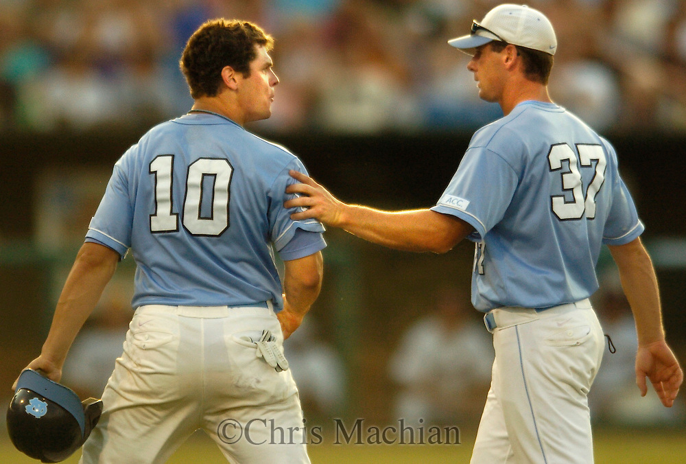 06/20/2006 North Carolina's Jay Cox is ushered off the field by first base coach Jason Howell during the ninth inning during game eleven of the College World Series in Omaha Nebraska Wednesday afternoon. Cox was called out on a close play with a sacrifice bunt..(photo by Chris Machian/Prairie Pixel Group)