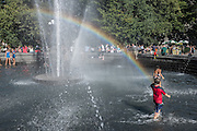 Children play under a rainbow on a hot summer day in the fountain in Washington Square Park.