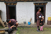 A traditional Puja celebration, a yearly Buddhist festival by the local community, Chuchizshey temple, Bumthang, Bhutan..Bhutan the country that prides itself on the development of 'Gross National Happiness' rather than GNP. This attitude pervades education, government, proclamations by royalty and politicians alike, and in the daily life of Bhutanese people. Strong adherence and respect for a royal family and Buddhism, mean the people generally follow what they are told and taught. There are of course contradictions between the modern and tradional world more often seen in urban rather than rural contexts. Phallic images of huge penises adorn the traditional homes, surrounded by animal spirits; Gross National Penis. Slow development, and fending off the modern world, television only introduced ten years ago, the lack of intrusive tourism, as tourists need to pay a daily minimum entry of $250, ecotourism for the rich, leaves a relatively unworldly populace, but with very high literacy, good health service and payments to peasants to not kill wild animals, or misuse forest, enables sustainable development and protects the country's natural heritage. Whilst various hydro-electric schemes, cash crops including apples, pull in import revenue, and Bhutan is helped with aid from the international community. Its population is only a meagre 700,000. Indian and Nepalese workers carry out the menial road and construction work.