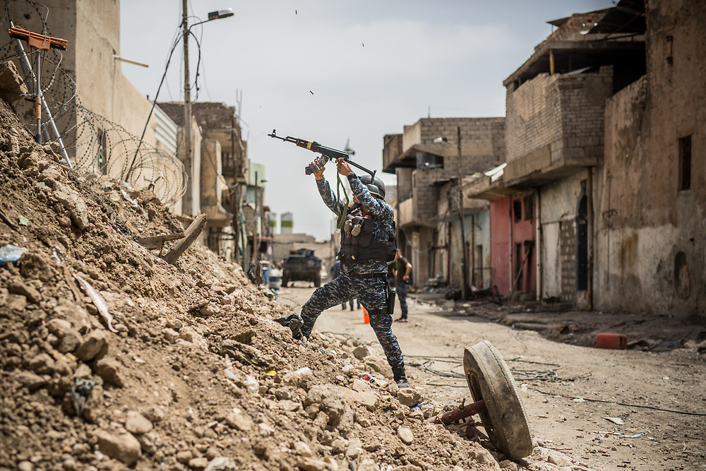 An Iraqi Federal Police Forces' officer fires a rifle to ISIS at the front line in West Mosul, Iraq.<br /> <br /> モスル西部のフロントラインで、ISISに向けてライフルを撃つイラク連邦警察軍。2017年5月撮影。