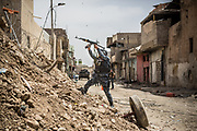 An Iraqi Federal Police Forces' officer fires a rifle to ISIS at the front line in West Mosul, Iraq.<br />